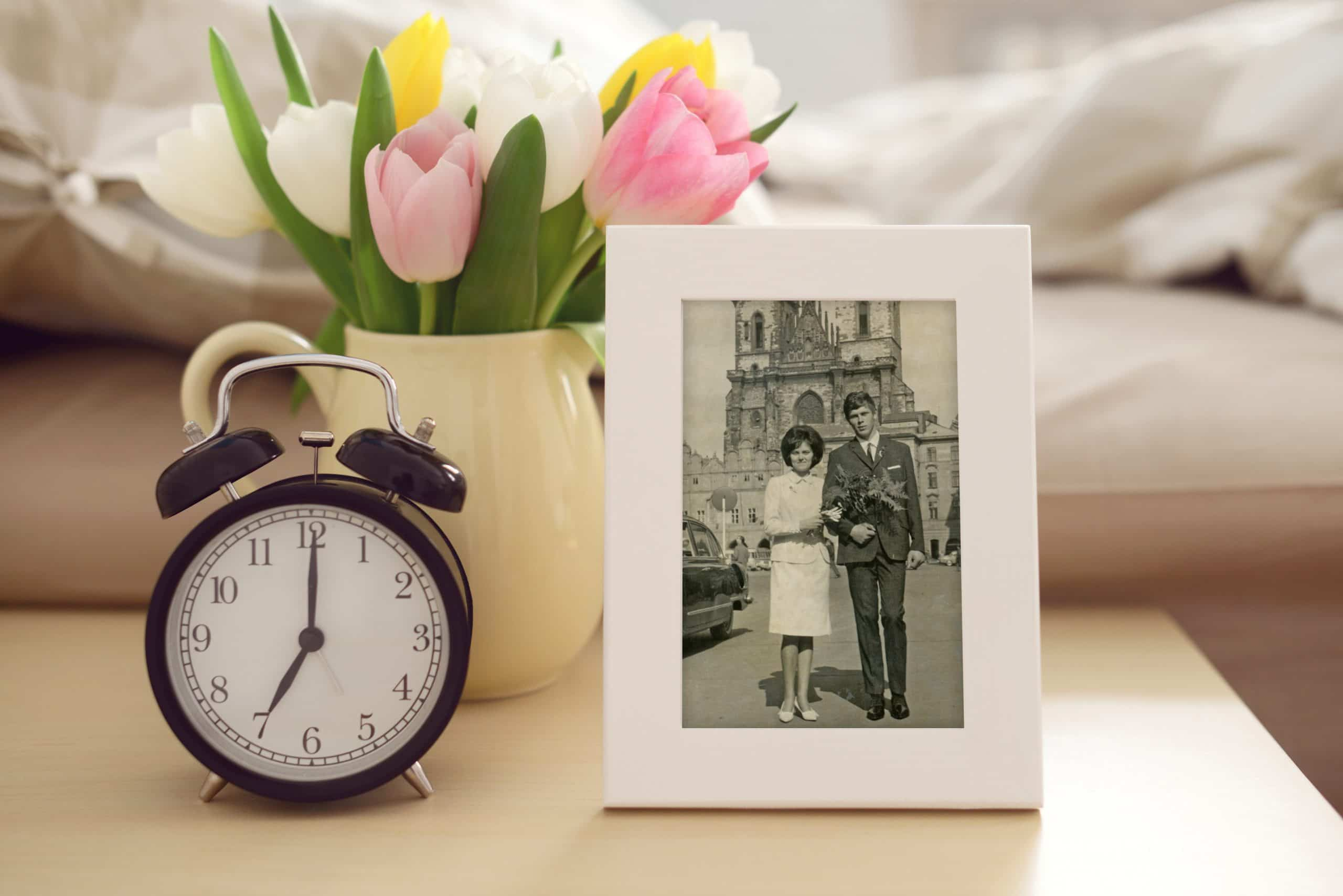 Analogue Clock, Frame Photo and Tulips on nightstand beside bed