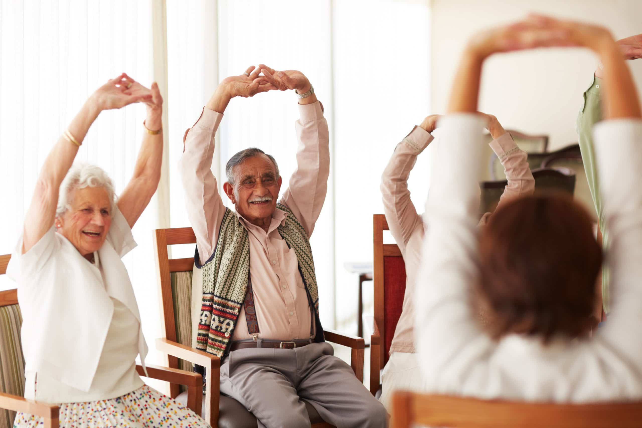 A group of elderly people doing stretching exercises with an instructor